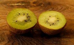 Fermez-vous sur un kiwi dédoublé dans la moitié sur une planche à découper en bois Kiwis vert clair avec les graines noires image libre de droits