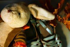 Fermez-vous sur un vieux jouet bourré de peluche de lapin se trouvant sur une paire de sandales colorées en pastel pâles images stock