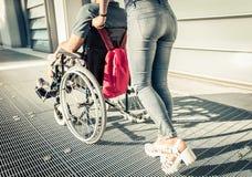Fermez-vous sur une femme poussant le fauteuil roulant avec son ami photos stock