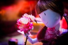 Fermez-vous sur une poupée de jouet tenant les roses roses Images stock