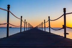 Fermez-vous, un pont foncé en bois près de la mer au coucher du soleil orange lumineux, backgound, texture, papier peint, vue rom Photo stock