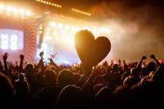 Fermez-vous vers le haut d'un coeur parmi la foule des personnes à pendant un concert vivant Photographie stock libre de droits