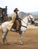 Fermez-vous vers le haut d'un cowboy conduisant son cheval dans la ville Photo stock