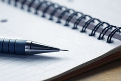 Fermez-vous vers le haut d'un crayon lecteur sur un bloc - notes Image stock