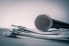 Fermez-vous vers le haut d'un microphone avec le document sur papier, concept du haut-parleur o photo libre de droits