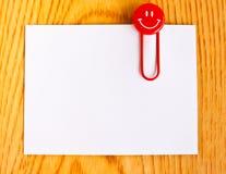Fermez-vous vers le haut d'un trombone rouge et d'un livre blanc Image stock