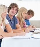 Fermez-vous vers le haut d'un étudiant de sourire avec des amis regardant l'appareil-photo Image libre de droits