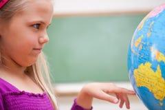 Fermez-vous vers le haut d'une écolière regardant un globe Photos libres de droits
