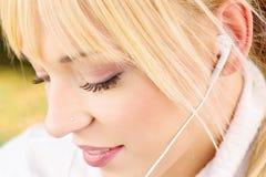 Fermez-vous vers le haut d'une femme avec des écouteurs Photo libre de droits