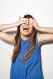 Fermez-vous vers le haut d'une jeune femme heureuse couvrant ses yeux images stock