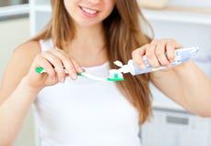 Fermez-vous vers le haut d'une jeune femme mettant la pâte dentifrice Photographie stock libre de droits
