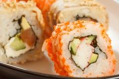 Fermez-vous vers le haut d'Uramaki la Californie Petit pain de sushi avec le nori, riz, morceaux Photo stock