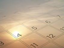 Fermez-vous vers le haut de le 4ème juillet à la page transparente de calendrier avec le fond brouillé de coucher du soleil de ci Photographie stock