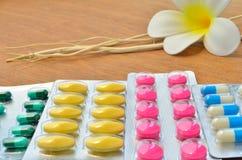 Fermez-vous vers le haut de coloré des comprimés et des capsules de médecine avec la fleur blanche et la branche d'arbre sèche Photo libre de droits