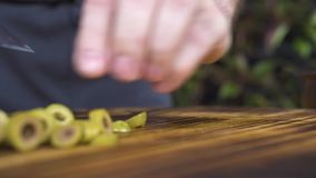 Fermez-vous vers le haut de couper les olives vertes avec le couteau sur la table en bois Mains de cuisinier de chef coupant en t clips vidéos