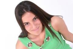 Fermez-vous vers le haut de de l'adolescence en vert avec le sourire au-dessus du blanc image stock