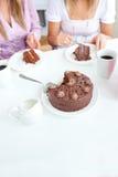 Fermez-vous vers le haut de deux femmes mangeant le gâteau de chocolat Image stock