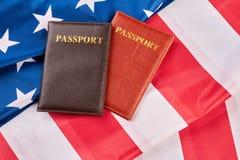 Fermez-vous vers le haut de deux passeports sur le drapeau américain photographie stock libre de droits