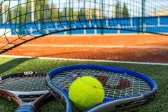 Fermez-vous vers le haut de deux raquettes de tennis et d'une boule sur le filet proche au sol sur le court de tennis photographie stock