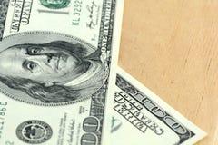 Fermez-vous vers le haut de 100 dollars de billets de banque sur le fond en bois Photographie stock libre de droits