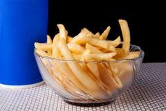 Fermez-vous vers le haut de Fried French Fries au bol en verre et à l'arrière-plan noir Image libre de droits