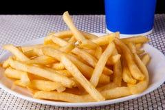 Fermez-vous vers le haut de Fried French Fries dans le plat blanc et la boisson non alcoolisée Photographie stock libre de droits
