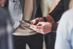 Fermez-vous vers le haut de jeunes amis regardant le téléphone intelligent tout en se reposant en café Personnes de métis dans le Photos stock
