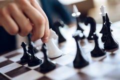Fermez-vous vers le haut de l'échiquier avec le chevalier blanc entouré par les chiffres noirs Photo stock