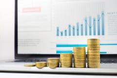 Fermez-vous vers le haut de l'élevage empilé par pièce de monnaie sur le diagramme financier de graphique dans l'ordinateur porta Photo stock