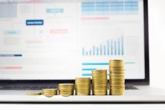 Fermez-vous vers le haut de l'élevage empilé par pièce de monnaie sur le diagramme financier de graphique dans l'ordinateur porta Images stock