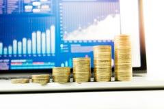 Fermez-vous vers le haut de l'élevage empilé par pièce de monnaie sur le diagramme financier de graphique dans l'ordinateur porta Photos stock