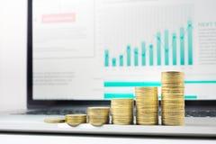 Fermez-vous vers le haut de l'élevage empilé par pièce de monnaie sur le diagramme financier de graphique dans l'ordinateur porta Image stock