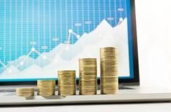 Fermez-vous vers le haut de l'élevage empilé par pièce de monnaie sur le diagramme financier de graphique dans l'ordinateur porta Photographie stock libre de droits