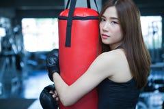fermez-vous vers le haut de l'étreinte de femme de boxeur poinçonnant le sac rouge avec des gants de boxe i images stock
