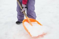 Fermez-vous vers le haut de l'adolescente pellant la neige du chemin Photo libre de droits