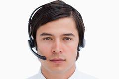 Fermez-vous vers le haut de l'agent mâle de centre d'attention téléphonique avec l'écouteur en fonction Image libre de droits