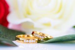 Fermez-vous vers le haut de l'anneau d'or et des roses rouges sur le blanc Photo stock