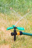 Fermez-vous vers le haut de l'arroseuse de pelouse en jour d'été Photos libres de droits