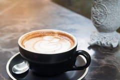Fermez-vous vers le haut de l'art de latte de café dans la tasse noire sur la texture de marbre, luxe photographie stock libre de droits