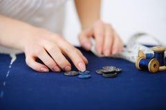 Fermez-vous vers le haut de l'atelier de couture de bouton de sélection de doigts d'ouvrière couturière Photo stock