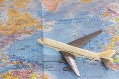 Fermez-vous vers le haut de l'avion blanc de jouet sur le fond de carte du monde Photo libre de droits