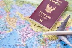 Fermez-vous vers le haut de l'avion et du passeport blancs de jouet sur le Ba de carte du monde Images libres de droits