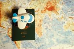 Fermez-vous vers le haut de l'avion et du passeport de jouet sur le fond de carte du monde Concept de voyage et d'affaires Photographie stock libre de droits