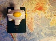 Fermez-vous vers le haut de l'avion et du passeport de jouet sur le fond de carte du monde Concept de voyage et d'affaires Images libres de droits