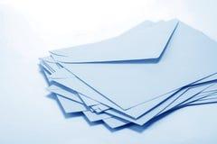 fermez-vous vers le haut de l'empilement des enveloppes et expédiez le papier de lettre sur b blanc Photos stock