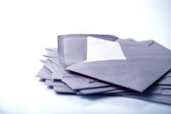 fermez-vous vers le haut de l'empilement des enveloppes et expédiez le papier de lettre sur b blanc Image libre de droits