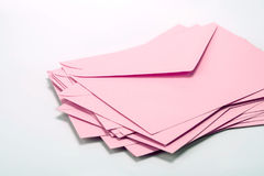 fermez-vous vers le haut de l'empilement des enveloppes roses et expédiez le papier de lettre sur le whi Photographie stock libre de droits