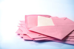 fermez-vous vers le haut de l'empilement des enveloppes roses et expédiez le papier de lettre sur le whi Image libre de droits