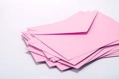 fermez-vous vers le haut de l'empilement des enveloppes roses et expédiez le papier de lettre sur le whi Images libres de droits