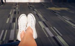 Fermez-vous vers le haut de l'espadrille blanche croisée d'usage de jambe étendue sur la valise à l'airpo Image stock